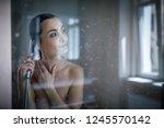 woman taking a long hot shower... | Shutterstock . vector #1245570142