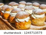 Small photo of Traditional winter sweet: Semla or semlor, flavored with cardamom, filled with almond paste & whipped cream from Sweden, Finland, Estonia, Norway & Denmark for Shrove Monday, fat Tuesday & Easter