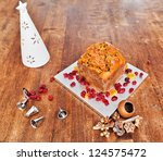 Christmas cake and white candle on wooden table - stock photo