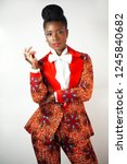Small photo of Portrait of a stylish young African woman wearing a colorful pant suit standing against a gray background