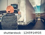 Trucker Adjusting Temperature in the Refrigerated Semitrailer. Transportation Industry Theme. - stock photo