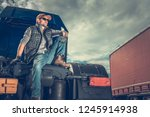 Proud Truck Owner. Transportation and Logistic Company.  Caucasian Men Relaxing on the Semi Tractor.  - stock photo