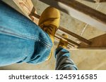Construction Worker on Wooden Ladder. Shoes Closeup Photo.  - stock photo