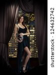 Seductive lady in evening dress with mask in her hands standing near the window, night city background - stock photo