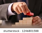 male hand holds red wood block... | Shutterstock . vector #1246801588