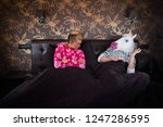 serious girl in pajama sits on... | Shutterstock . vector #1247286595