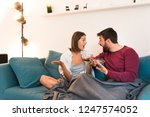 cute happy couple sitting on... | Shutterstock . vector #1247574052