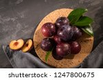 delicious red plums in a cork... | Shutterstock . vector #1247800675