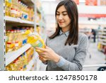woman choosing sunflower oil in ... | Shutterstock . vector #1247850178