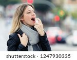 Small photo of Shot of illness young woman using a analgesic spray to soften the throat in the street.