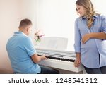 happy husband playing piano to...   Shutterstock . vector #1248541312