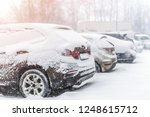 Cars parked in row at outdoor parking in winter. Vehicles covered by snow during heavy snowfall. snowstorm or blizzard weather forecast - stock photo