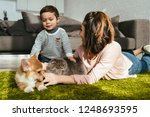 Stock photo mother and son laying on floor with dog and cat in living room at home 1248693595