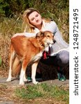 Stock photo pretty girl with his shetland sheepdog dog at nature park outdoor is standing and posing in front 1248721495