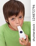 Boy with inhaler - asthma and other respiratory illnesses concept - stock photo