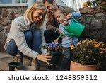 little boy watering flowers... | Shutterstock . vector #1248859312