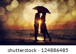 Stock photo couple kissing under umbrella at the beach in sunset photo in old image style 124886485