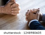 Small photo of Businesspeople at business meeting making decision thinking unrecognizable businessmen sitting opposite of each other, close up hands clenched resting on desk. Opposition and nervous situation concept