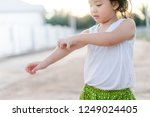 Small photo of Little asian girl scratching an itch with hand outdoor.Kid's hand scratch itchy from allergy.Sensitive Skin, Food allergy symptoms, Irritation.