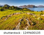 Wanaka lake coast line and highlands, Glendhu bay view. Nice track on shore with beautiful green meadow, hills, rocks and snowy mountains in background. Wild New Zealand nature. Landscape panorama.