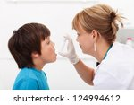 Boy having respiratory illness helped by health professional with inhaler - stock photo