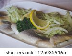 Stock photo tasty herring with lemon on a white plate 1250359165