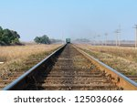 old railroad with train goes to horizon - stock photo