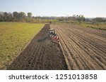 a farmer on a red tractor with... | Shutterstock . vector #1251013858