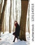 Small photo of Portrait of young womqn in stylish coat and sunglasses standing near the tree tunk in the snowy park on sunny winter day