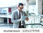 smiling businessman using... | Shutterstock . vector #1251175705