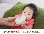 mother holding and feeding... | Shutterstock . vector #1251450568