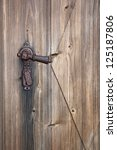 Ancient rusty door handle on brown old wooden door - stock photo