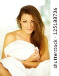 Woman on bed wrapped in blanket and smiling - stock photo
