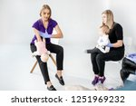 Small photo of Young mother with baby during the first aid training with instructor showing on baby dummy how to help to the suffocating child