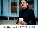 Half length portrait of confident financial economist in optical eyewear waiting for call from business partner while standing on urban setting with coffee to go in hand, concept of entrepreneurship