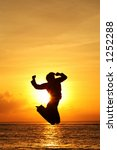 Silhouette of happy woman jumping at beach - stock photo
