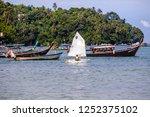 Small photo of Phuket, Thailand – November 25, 2018: People sailing sailboat across Bang Tao Bay Pier, Bang Tao Beach, Phuket, Thailand.