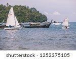 Small photo of Phuket, Thailand – November 25, 2018: Tourists sailing sailboats across Bang Tao Bay Pier, Bang Tao Beach, Phuket, Thailand.