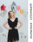 Small photo of Beautiful young caucasian woman in balck dress, confident and unfriendly posing stare at camera, white background and colorful festive balloons, portrait studio shot.