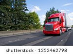 Small photo of Bright red bonnet American modern long haul big rig semi truck with dry van semi trailer transporting commercial cargo moving on the wide multiline green highway road
