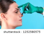 cosmetic surgeon examining... | Shutterstock . vector #1252580575