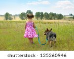 Stock photo little girl walking with dog at the meadow and keeping the dog on leash 125260946