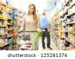 Young woman shopping in a supermarket - stock photo