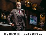 Stock photo portrait of wealthy prosperious senior businessman in drinking coffee near bar counter at elite 1253150632