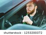 a drunken man driving a car... | Shutterstock . vector #1253200372