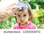 mother cutting her baby's hair... | Shutterstock . vector #1253343472