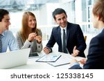 Stock photo image of business partners discussing documents and ideas at meeting 125338145