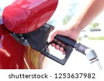 male hand fills a red car at a... | Shutterstock . vector #1253637982