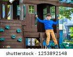 little boy climbing ladder on... | Shutterstock . vector #1253892148