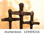 Easter image of rusty nail crosses with gold fabric and defocused lights as background.  Macro with shallow dof. - stock photo